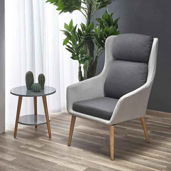 Интериор с модерно сиво кресло с висока облегалка и тъмни възглавници
