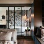 Спалня и баня разделени със стъклена преграда