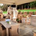 Външна кухня с каменна облицовка, барбекю, пещ и маса за хранене