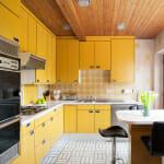 Жълта кухня с дървен таван - Stacy Naquin Interiors